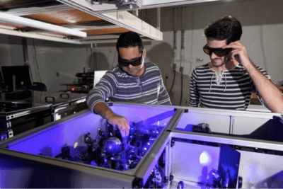 Carlos Silva (l.) in his lab at Georgia Tech with graduate research assistant Félix Thouin examining a setup to process laser light in the visible range for the testing of quantum properties in a halide organic-inorganic perovskite. Image: Georgia Tech/Rob Felt